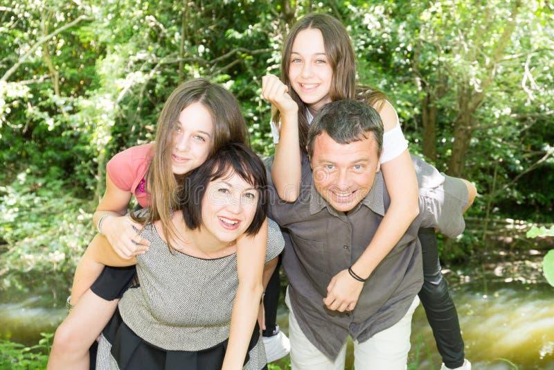 Familj av fyra utomhus- förälskat för lek på ryggen royaltyfria foton