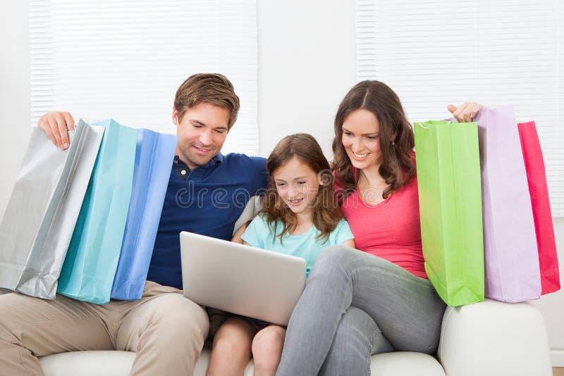 Familj av med shoppingpåsar genom att använda bärbara datorn arkivfoton