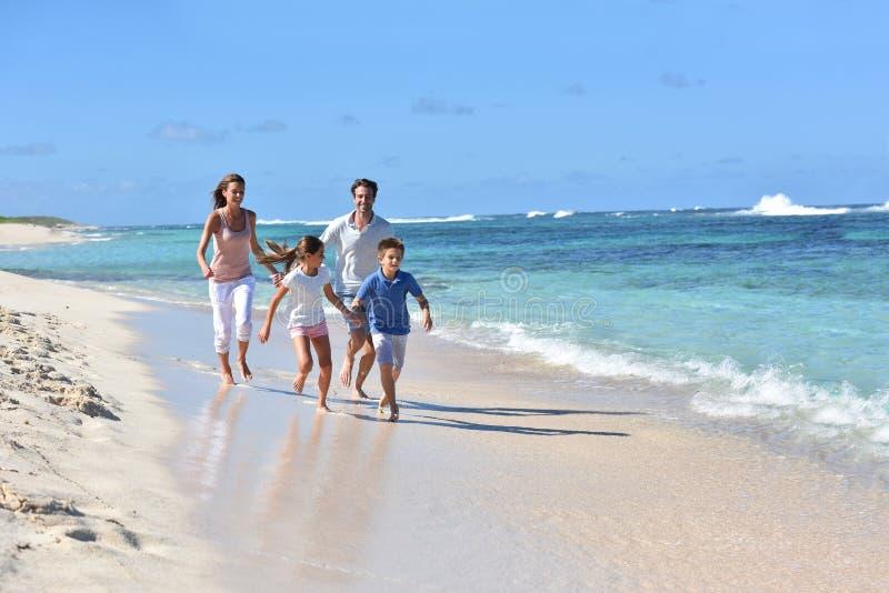 Familj av runinng fyra på stranden i vändkretsar royaltyfri foto