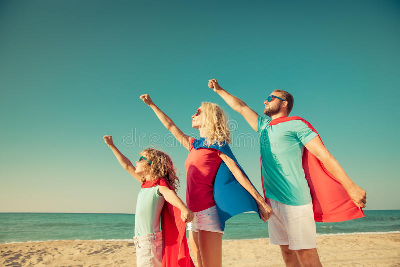Familj av superheroes på stranden Resa resväskan med seascapeinsida royaltyfria foton