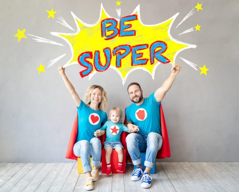 Familj av superheroes som hemma spelar royaltyfri fotografi
