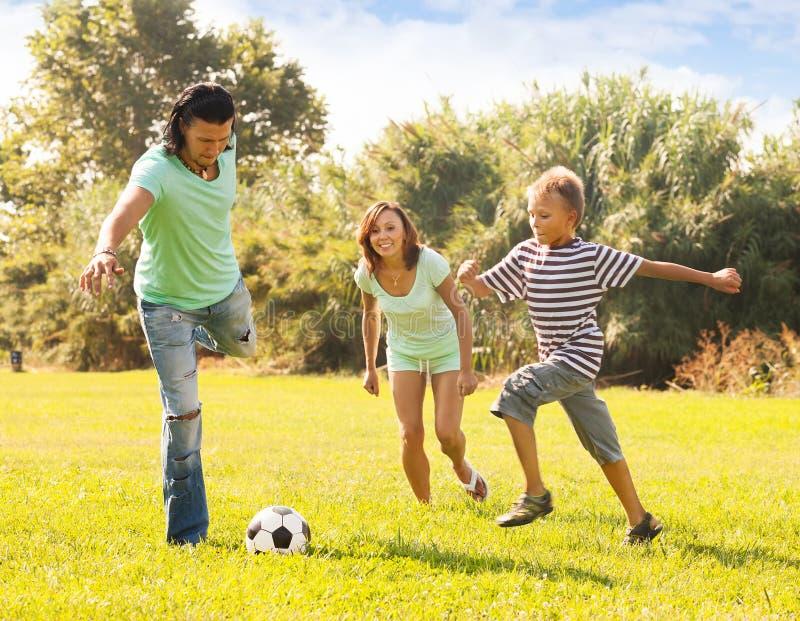 Familj av tre med tonåringen som spelar i fotboll royaltyfri bild