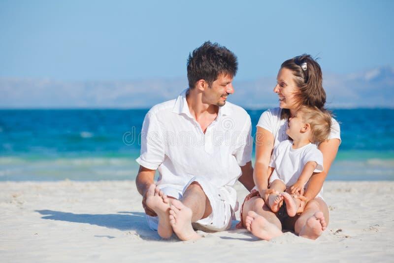 Familj av tre på den tropiska stranden royaltyfri fotografi