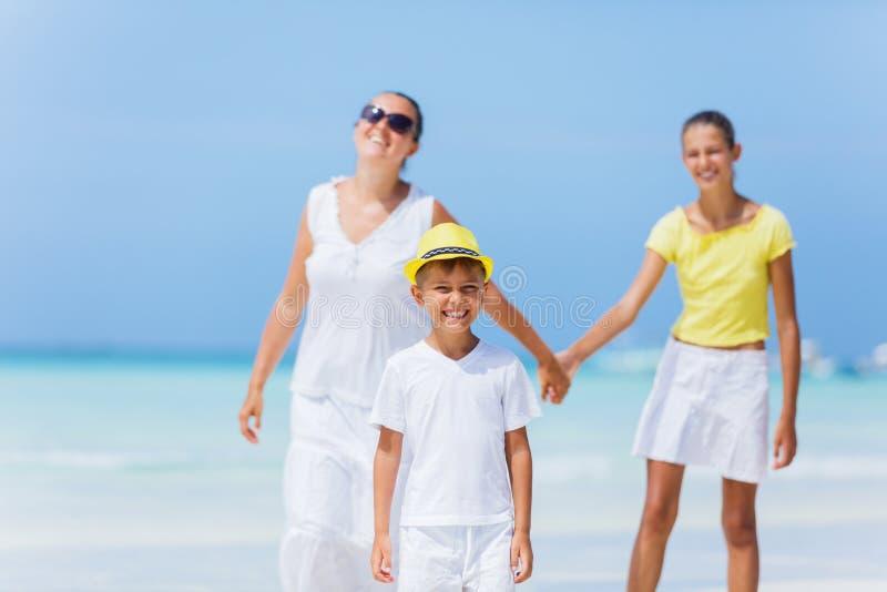 Familj av tre som går på stranden royaltyfri bild