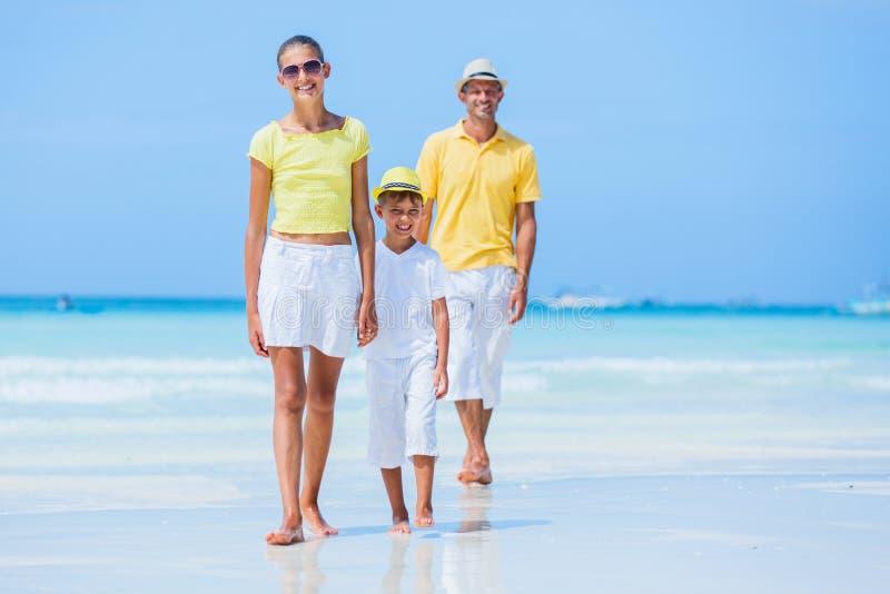 Familj av tre som går på stranden royaltyfria bilder