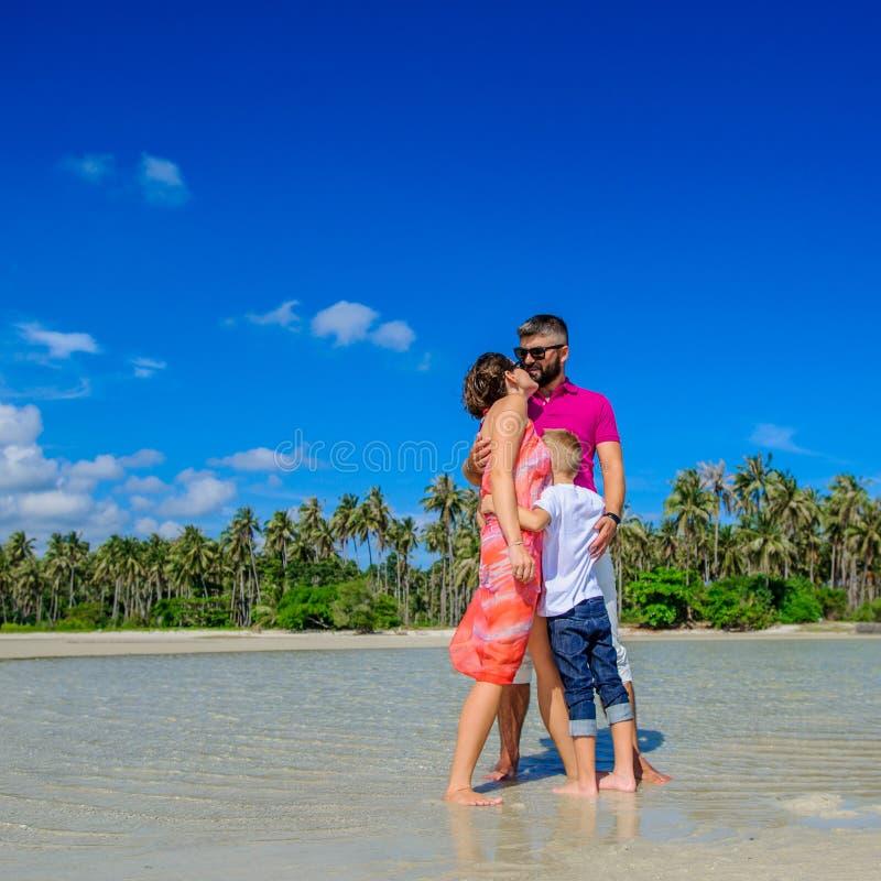 Familj av tre som kör längs den tropiska för skratta och enjoingtiden för strand, tillsammans royaltyfri bild