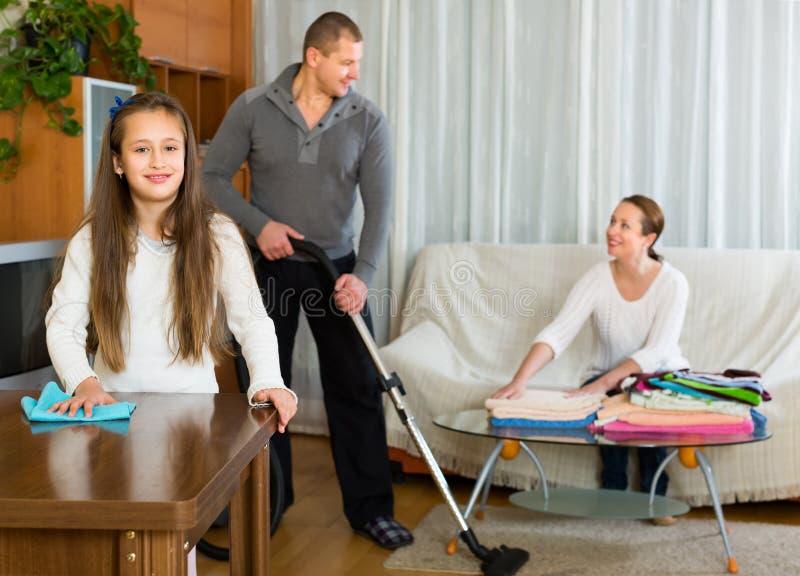 Familj av tre som ordnar ett rum arkivbild