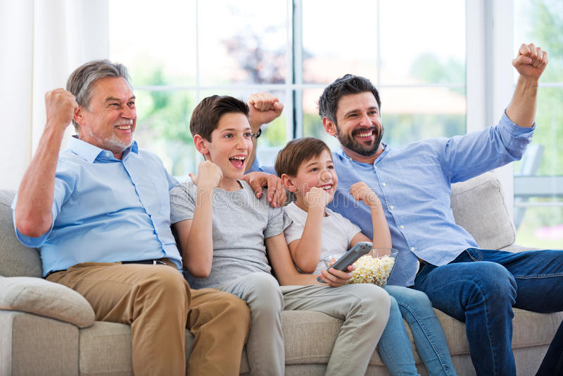 Familj av tre utvecklingar som håller ögonen på tv arkivbild