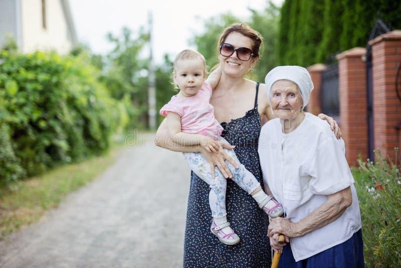 Familj av tre utvecklingar utomhus: hög kvinna, hennes vuxna sondotter och stor- sondotter för litet barn fotografering för bildbyråer