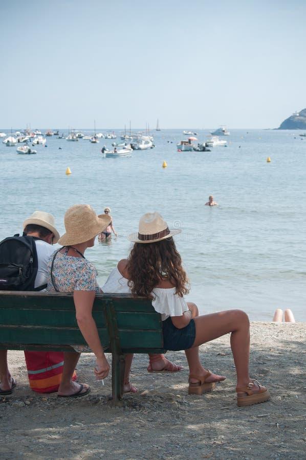 familj av turister med tonåringsammanträde på bänk nära stranden royaltyfri fotografi