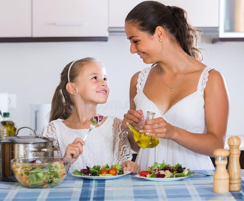 Familj av två som har sund lunch med veggies fotografering för bildbyråer