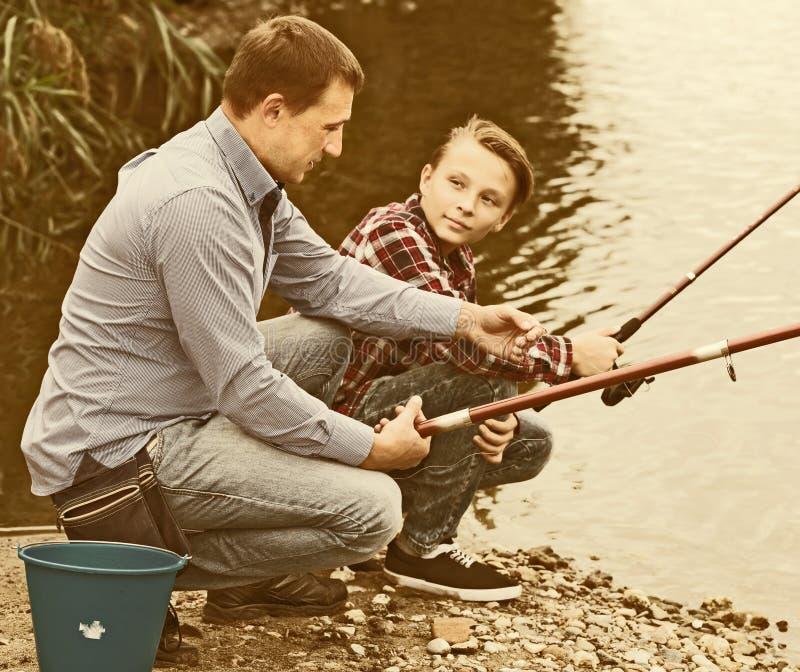 Familj av två som tillsammans fiskar på den sötvattens- sjön royaltyfri foto