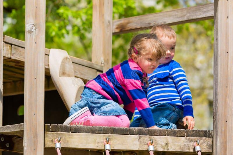Familj - barn som spelar på en klätterställning arkivfoto