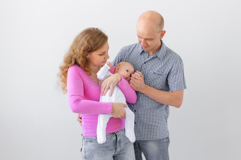 Familj-, barndom- och föräldraskapbegrepp - fadern, den gulliga modern som rymmer, behandla som ett barn över vit bakgrund royaltyfria foton