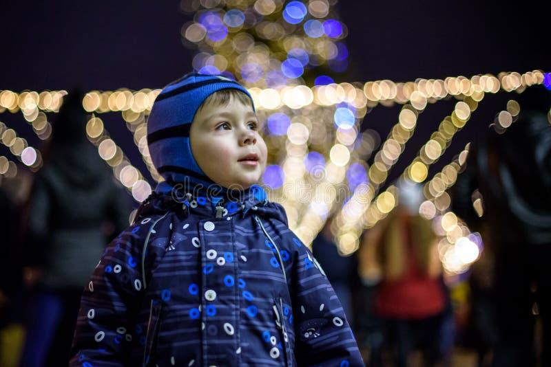 Familj, barndom, säsong och folkbegrepp - som är lyckligt i vinterkläder över snöig stadsbakgrund royaltyfri fotografi