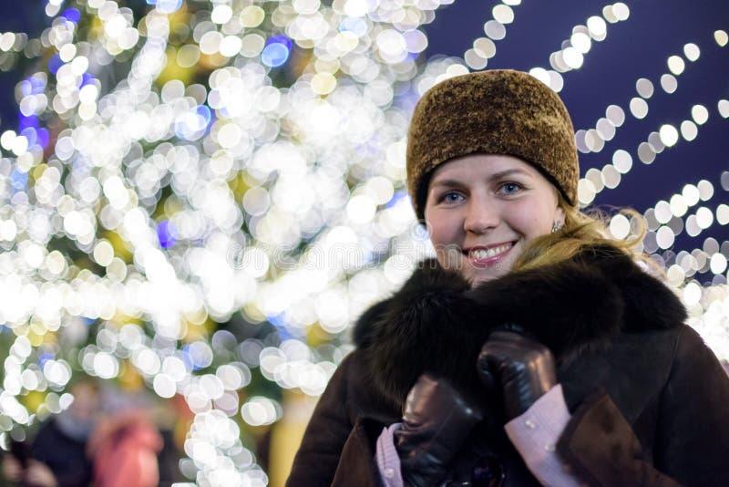 Familj, barndom, säsong och folkbegrepp - som är lyckligt i vinterkläder över snöig stadsbakgrund royaltyfria foton