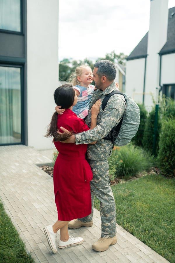 Familj efter möte medan make som går tillbaka från militärtjänst royaltyfri foto