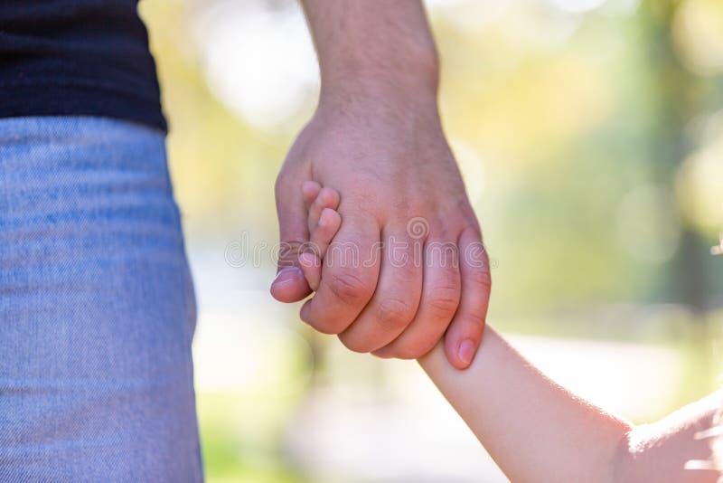 Familj, föräldraskap, faderskap, adoption och folkbegrepp - lycklig fader och liten flicka som går att rymma i hand in royaltyfri foto