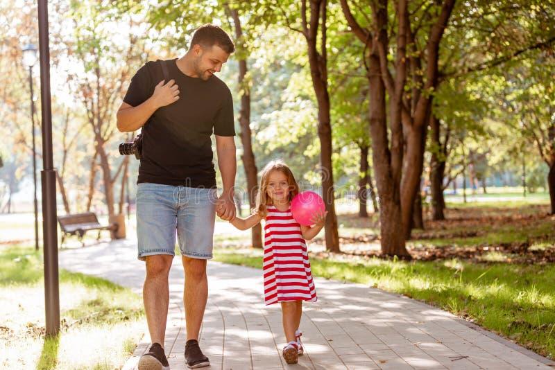 Familj, föräldraskap, faderskap, adoption och folkbegrepp - lycklig fader och liten flicka som går att rymma i hand in arkivbild