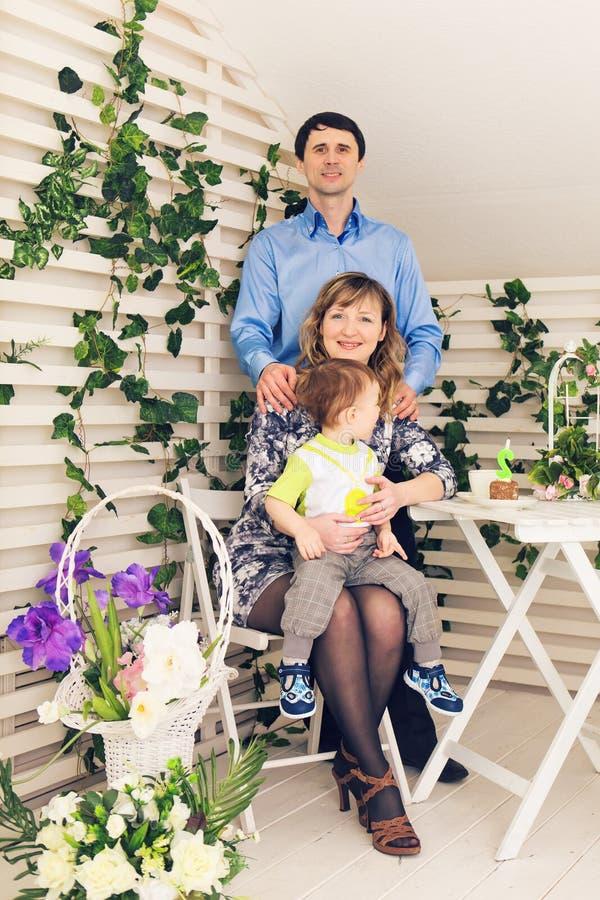 Familj, föräldraskap, lycklig födelsedag och feriebegrepp - stående av lyckliga föräldrar och barnet på en tabell som dricker te  royaltyfri fotografi