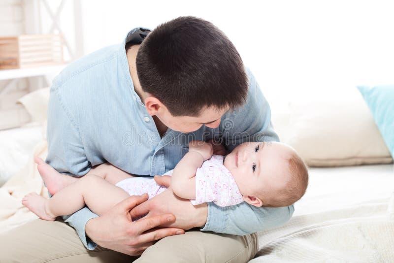 Familj, föräldraskap och folkbegrepp - fadern med litet behandla som ett barn hemma arkivbild