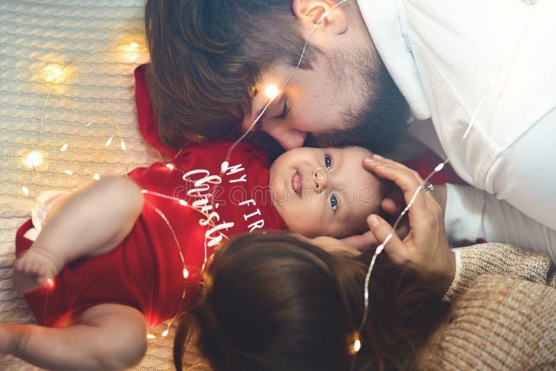 Familj förälskelse, lyckabegrepp Föräldrar som kysser baby'sens kind lycklig familj arkivfoton