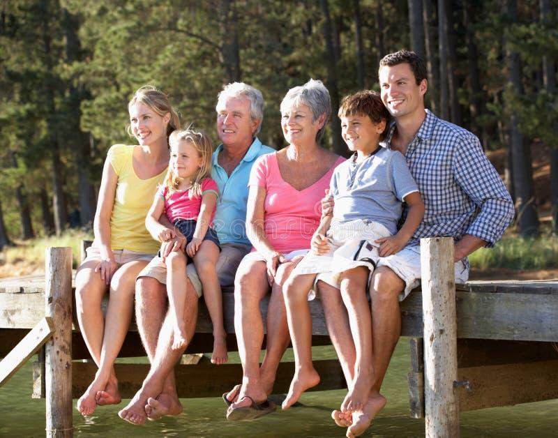 Familj för 3 utveckling som har gyckel vid en lake royaltyfri fotografi