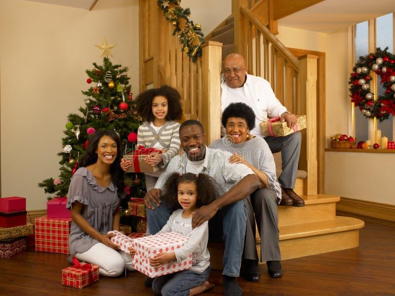 Familj för blandad race med julgranen och gåvor fotografering för bildbyråer