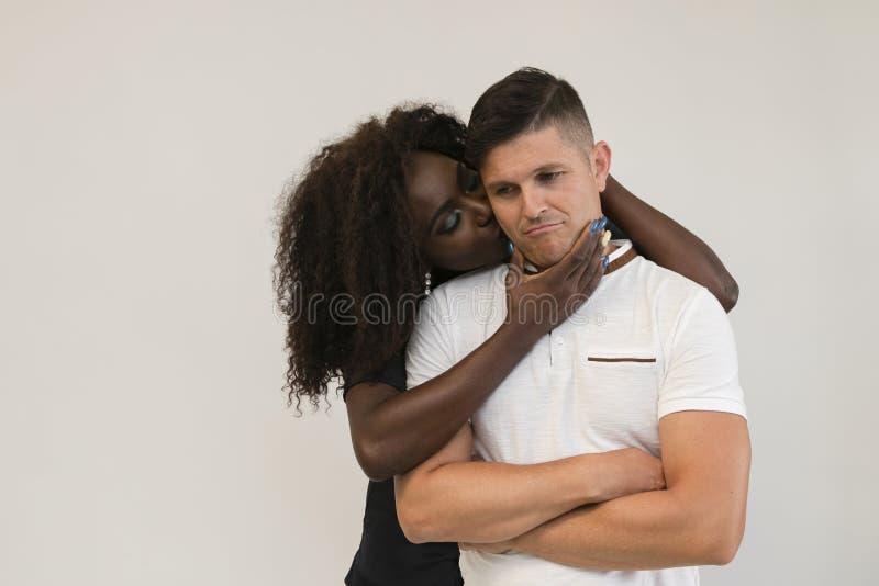 Familj för blandat lopp Barnet erbjuder frun som kramar hans make älska arkivfoton