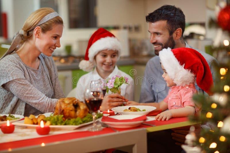"""Familj för jultid†som """"tycker om på julmatställe arkivbild"""