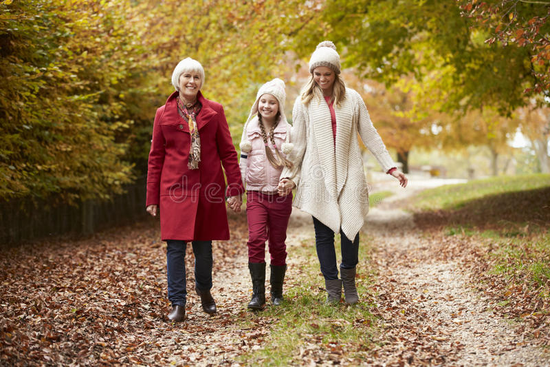 Familj för kvinnligMultl utveckling som promenerar Autumn Path arkivfoton