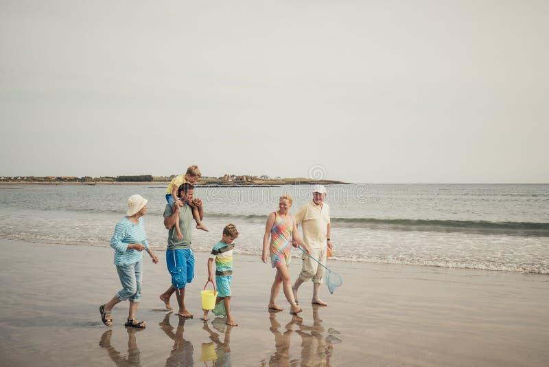 Familj för tre utveckling på en strand arkivbild