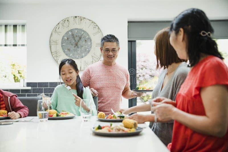 Familj för tre utveckling som har matställen arkivbilder