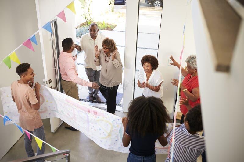Familj för tre utveckling som kastar ett överraskningparti som välkomnar gäster på ytterdörren, högstämd sikt royaltyfria bilder