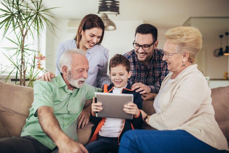 Familj för tre utveckling som spenderar tid som använder tillsammans hemma den digitala minnestavlan arkivbilder
