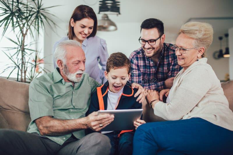 Familj för tre utveckling som spenderar tid som använder tillsammans hemma den digitala minnestavlan arkivfoto