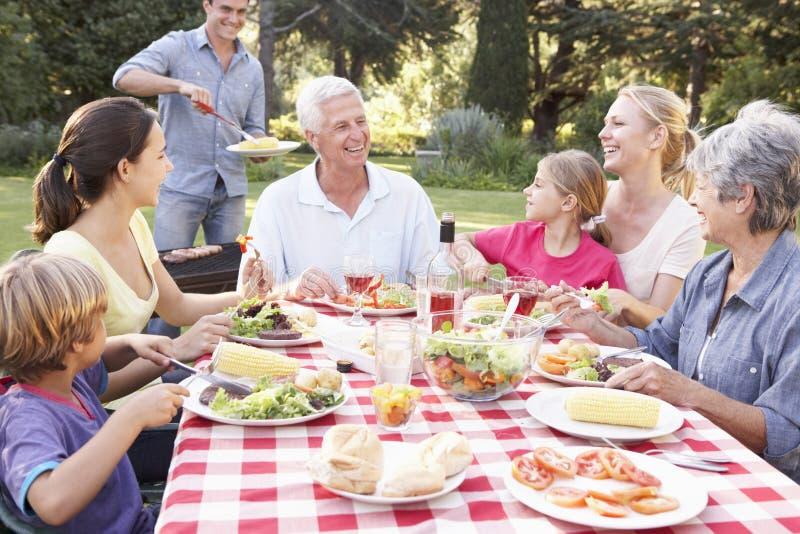 Familj för tre utveckling som tillsammans tycker om grillfesten i trädgård arkivbilder