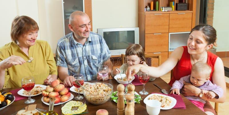 Familj för tre utvecklingar som har lunch arkivbild