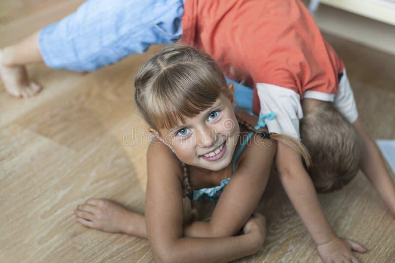 familj Förtjusande liten flicka, medan spela med hennes lilla broder arkivfoto