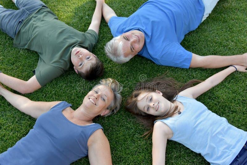 Familj, fader, moder, son och dotter som ligger i ängen arkivbilder