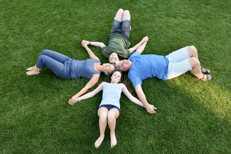 Familj, fader, moder, son och dotter som ligger i ängen royaltyfri fotografi