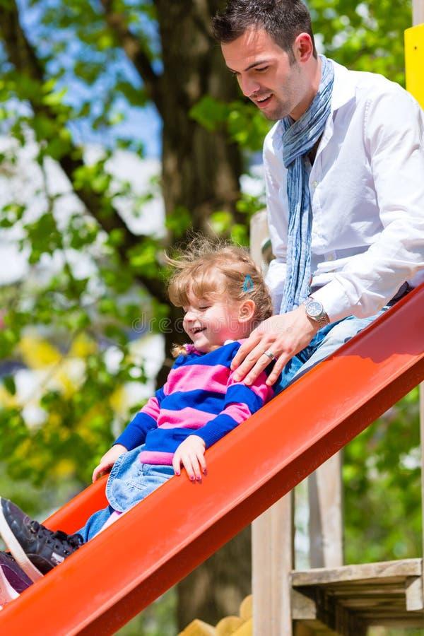 Familj - fader och dotter som spelar på en klätterställning royaltyfri bild