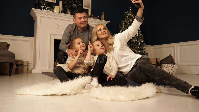Familj, ferier, teknologi och folk - le modern, fadern och små flickor som gör selfie med kameran över arkivbild