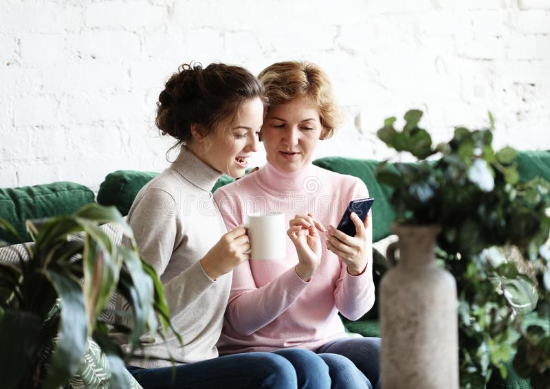 Familj, folk och teknologibegrepp: Åldrig kvinna och hennes vuxna dotter som hemma använder smartphonen arkivfoto