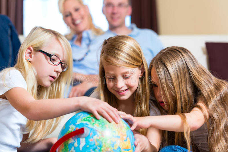 Familj hemma, barnen som leker med ett jordklot royaltyfri fotografi