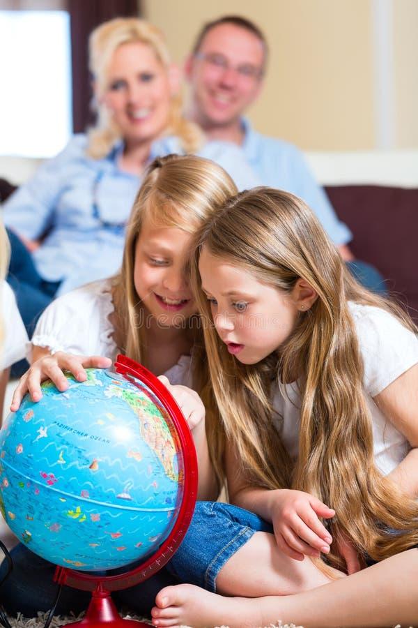 Familj hemma, barnen som leker med ett jordklot arkivfoto