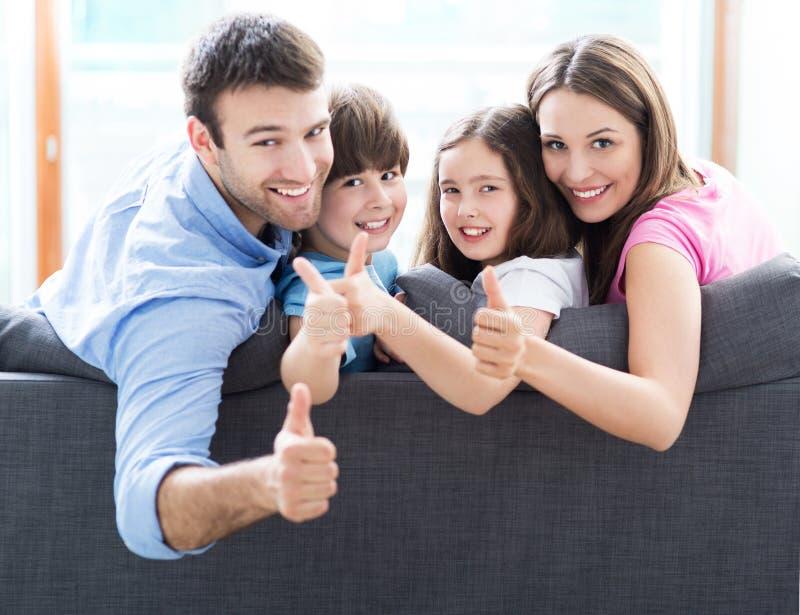 Familj hemma med tummar upp arkivbild