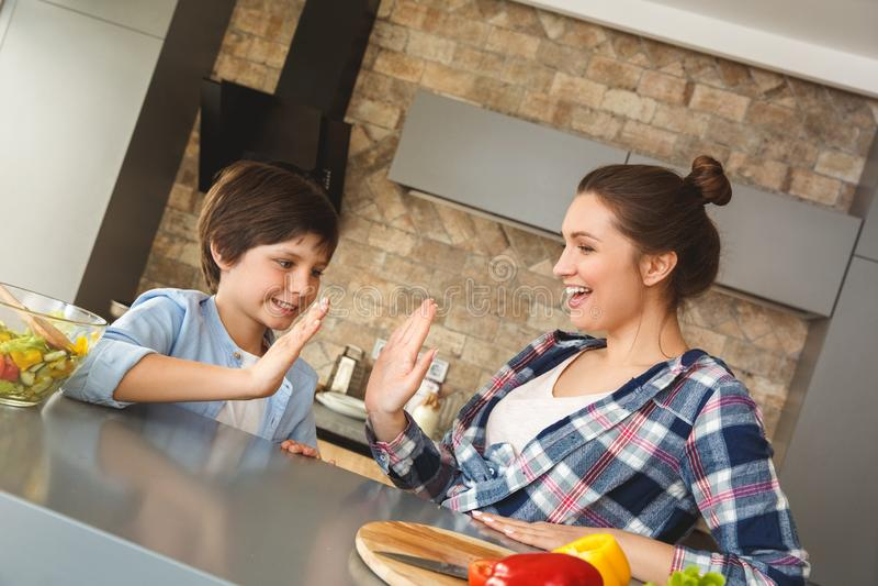 Familj hemma som lutar på tabellen i kök som ger tillsammans högt fem att le som är positivt royaltyfria bilder