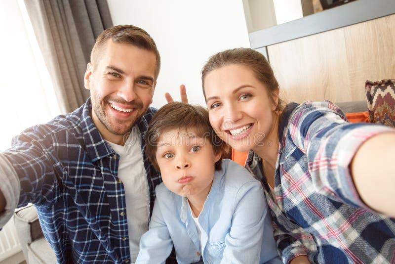 Familj hemma som sitter på soffan i vardagsrum som tar tillsammans selfiebildföräldrar som gör horn till sonen gladlynta royaltyfri bild