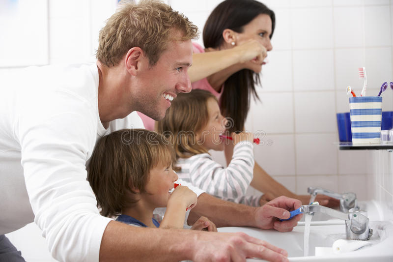 Familj i badrum som borstar tänder arkivfoton